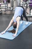 Yoga practicante de la mujer atractiva joven, colocándose en ejercicio boca abajo del perro Fotografía de archivo
