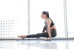Yoga practicante de la mujer atractiva joven, sentándose en ejercicio, resolviéndose, ropa de deportes que lleva en la ventana de Imagen de archivo libre de regalías