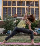 Yoga practicante de la mujer bastante joven en el parque (ángulo lateral extendido) Imagenes de archivo