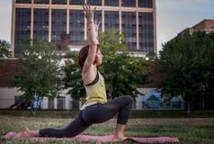 Yoga practicante de la mujer bastante joven en el parque (estocada baja) Imagen de archivo libre de regalías
