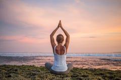 Yoga practicante de la mujer cauc?sica en la costa imagen de archivo