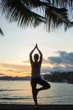 Yoga practicante de la mujer cauc?sica en la costa fotografía de archivo libre de regalías