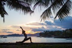 Yoga practicante de la mujer cauc?sica en la costa imagen de archivo libre de regalías