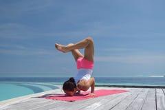 Yoga practicante de la mujer china asiática por el mar Imagenes de archivo