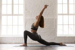 Yoga practicante de la mujer, colocándose en actitud del anjaneyasana, ejercicio del jinete del caballo imagen de archivo