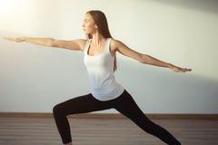 Yoga practicante de la mujer, colocándose en ejercicio del guerrero uno, Virabhadrasana Imagenes de archivo