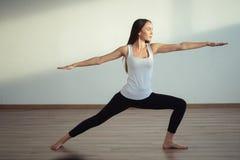 Yoga practicante de la mujer, colocándose en ejercicio del guerrero uno, Virabhadrasana Foto de archivo