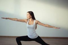 Yoga practicante de la mujer, colocándose en ejercicio del guerrero uno, Virabhadrasana Foto de archivo libre de regalías