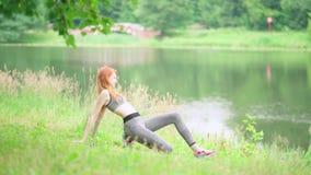 Yoga practicante de la mujer delgada hermosa en parque almacen de metraje de vídeo