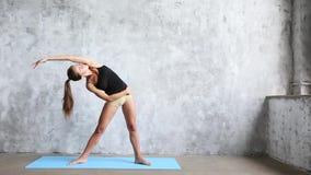 Yoga practicante de la mujer dentro en la estera azul metrajes
