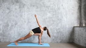 Yoga practicante de la mujer dentro en la estera azul almacen de metraje de vídeo