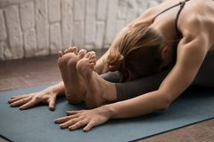 Yoga practicante de la mujer deportiva, actitud delantera asentada de la curva, paschimottanasana fotos de archivo