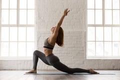 Yoga practicante de la mujer deportiva, colocándose en actitud del anjaneyasana, jinete del caballo fotografía de archivo