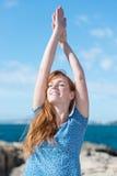 Yoga practicante de la mujer en el mar Imagenes de archivo