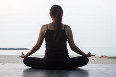 Yoga practicante de la mujer en el mar de la paz por mañana Fotografía de archivo