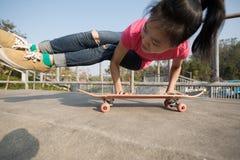 yoga practicante de la mujer en el monopatín en la rampa del skatepark fotografía de archivo