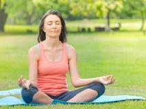 Yoga practicante de la mujer en parque Imagen de archivo libre de regalías
