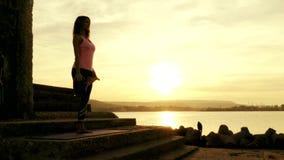Yoga practicante de la mujer en la playa en la puesta del sol almacen de metraje de vídeo