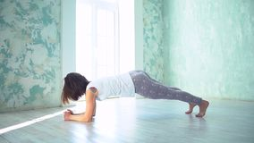 Yoga practicante de la mujer en un estudio brillante, atravesando saludos del sol Yoga que hace femenina en un estudio con natura almacen de metraje de vídeo