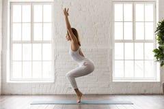 Yoga practicante de la mujer hermosa, colocándose en la actitud de Utkatasana, ejercicio de la silla fotos de archivo