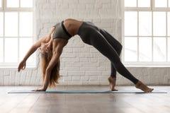 Yoga practicante de la mujer hermosa, colocándose en la actitud de Wild Thing, Camatkarasana foto de archivo