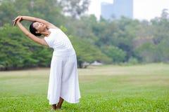 Yoga practicante de la mujer hermosa en el parque Imágenes de archivo libres de regalías