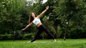 Yoga practicante de la mujer hermosa en el parque almacen de metraje de vídeo