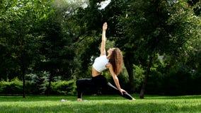 Yoga practicante de la mujer hermosa en el parque almacen de video