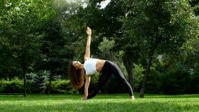 Yoga practicante de la mujer hermosa en el parque metrajes