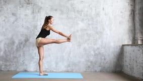 Yoga practicante de la mujer hermosa joven dentro en la estera azul almacen de metraje de vídeo