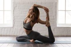 Yoga practicante de la mujer joven, actitud de la sirena, Eka Pada Rajakapotasana imagen de archivo