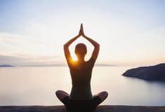 Yoga practicante de la mujer joven al aire libre Imágenes de archivo libres de regalías