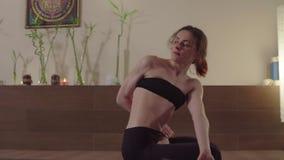 Yoga practicante de la mujer joven - Ardha Padmasana, torsi?n almacen de metraje de vídeo