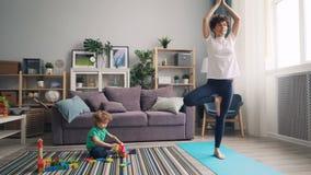 Yoga practicante de la mujer joven en casa mientras que niño tranquilo que juega con los juguetes en piso almacen de video