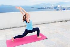 Yoga practicante de la mujer joven en el tejado del edificio Virabhadrasana Foto de archivo