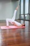 Yoga practicante de la mujer joven en la estera imagenes de archivo