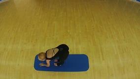 Yoga practicante de la mujer joven en la estera en el gimnasio almacen de video