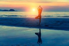 Yoga practicante de la mujer joven en la playa en la puesta del sol con la reflexión en agua imágenes de archivo libres de regalías