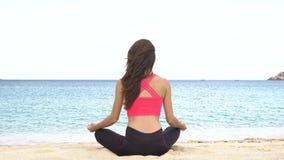 Yoga practicante de la mujer joven en la playa en la puesta del sol Ejercicios calma y armonía Meditación en actitud del loto San almacen de metraje de vídeo