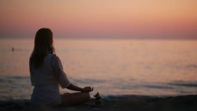 Yoga practicante de la mujer joven en la playa en la puesta del sol Mar tranquilo