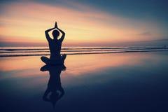 Yoga practicante de la mujer joven en la playa en la puesta del sol surrealista Foto de archivo libre de regalías