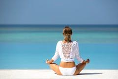 Yoga practicante de la mujer joven en la playa Maldivas imágenes de archivo libres de regalías