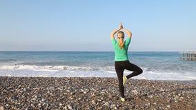 Yoga practicante de la mujer joven en la puesta del sol almacen de metraje de vídeo