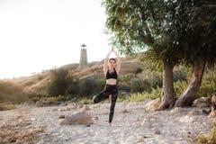 Yoga practicante de la mujer joven en la playa por puesta del sol imagenes de archivo
