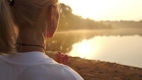 Yoga practicante de la mujer joven en la playa en la puesta del sol metrajes