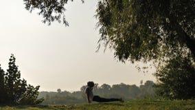 Yoga practicante de la mujer joven en la puesta del sol al aire libre almacen de metraje de vídeo