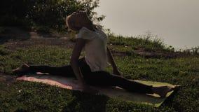 Yoga practicante de la mujer joven en la puesta del sol al aire libre metrajes