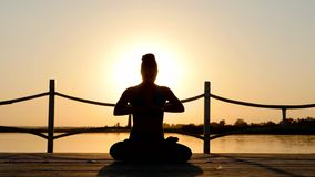 Yoga practicante de la mujer joven en sunflares en la playa en la puesta del sol metrajes