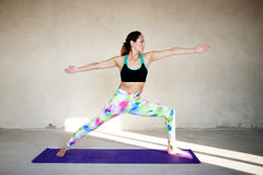 Yoga practicante de la mujer joven en un fondo urbano Foto de archivo