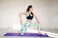 Yoga practicante de la mujer joven en un fondo urbano Foto de archivo libre de regalías
